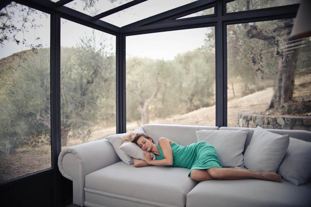 woman sleeping on a couch in front of windows