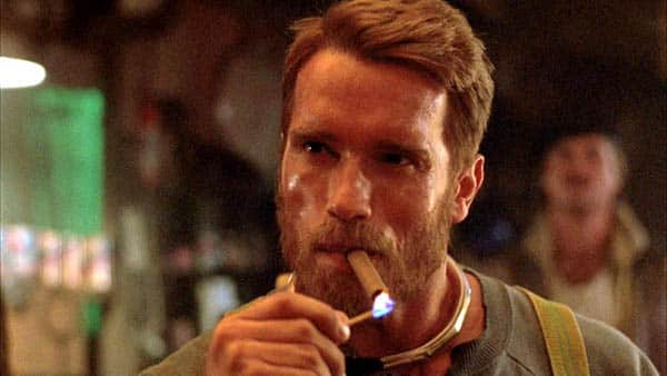 The Running Man - Arnold Schwarzenegger as Ben Richards lighting up a cigar and smoking a cigar