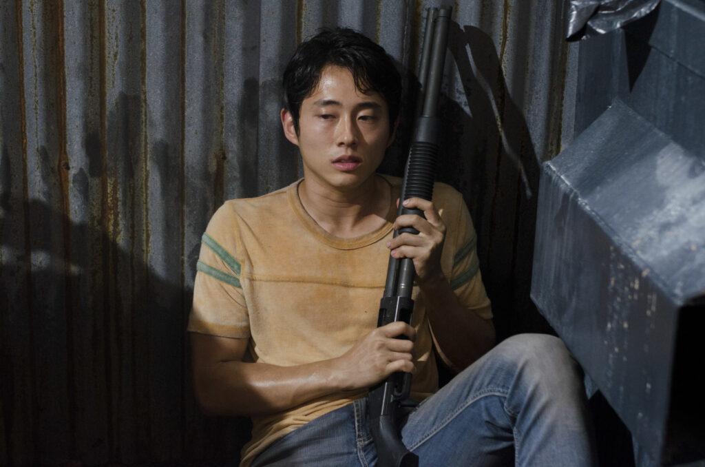 steven yeun glenn crouches with a shotgun